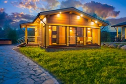 Country cottage in evening. Wooden house with panoramic windows. Night lighting at home. Concept - renting a country house. Rent of apartments in a picturesque location. Rent a house for the weekend