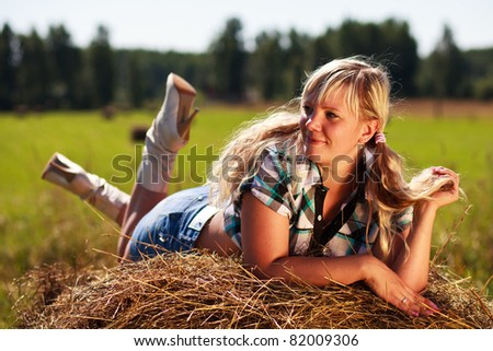 Country girl on straw bale.