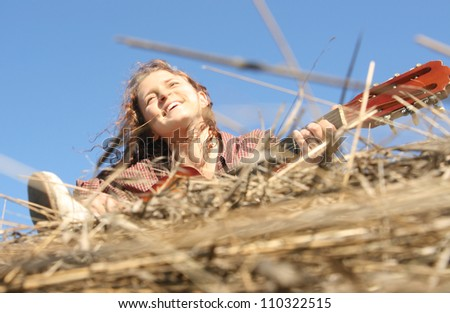 Country girl playing guitar at haystack