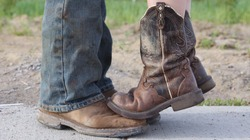 Country girl standing with tiptoes on cowboy's boots.  Short girl problems.