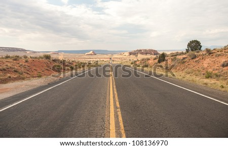 Country Highway with Straight road and dramatic sky . Shallow depth of field. A very Long road to Monument Valley