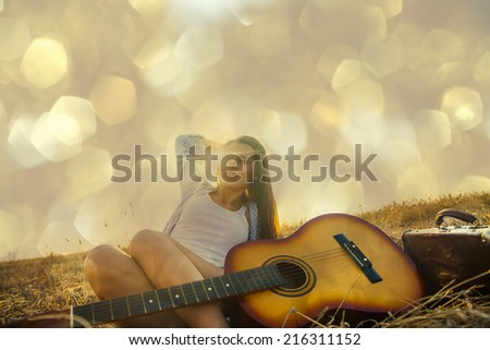 Country hippie girl with acoustic guitar at wheat field resting and relaxing near old retro suitcase Cute woman looking far away on horizon Sun shine rays on sky background Space for inscription