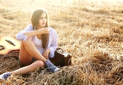 Country hippie girl with guitar at wheat field drinking black caffee from a mug thermos of relying on the old retro suitcase