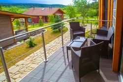 Country holiday. Terrace of a country house. Concept - abeautiful view opens from terrace. Armchairs and a table are on balcony. Concept - rental of a country house. Houses among northern nature.