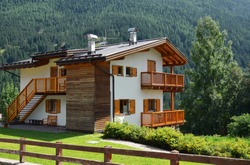 Country house in Alpine village. Sunny summer day. Dolomites, Val di Fassa, Italy.