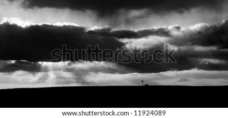 Country landscape showing a windmill in the distance following a storm