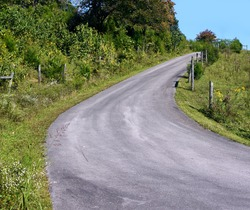 Country lane curves and tops a Tennessee hill.  Rustic fence posts line the road on both sides.