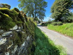 Country lane, with moss covered dry stone walls, leading down into the village of, Rylstone, Skipton, UK