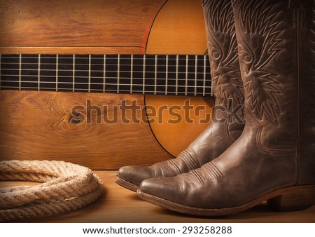 Country music with guitar and cowboy shoes on wood texture background