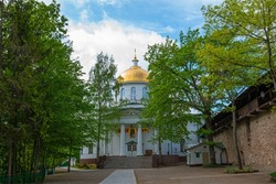 Country old church in Russia. Village stone church. Golden domes of a church with crosses on a background of blue clear skies. Domes of the church behind green trees on a clear day.