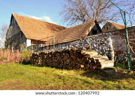 Country old house with pile of firewood in Romania