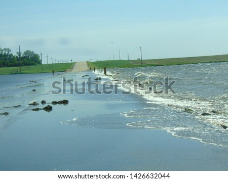 country road covered with water and debris on a windy day