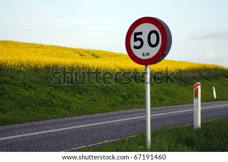 Country road with a yellow rape field and 50 kilometres speed limit traffic sign.