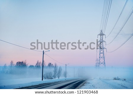 Country road with electricity pylons on foggy winter evening