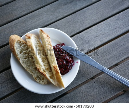 Country style breakfast: home made jam and bread on wooden table