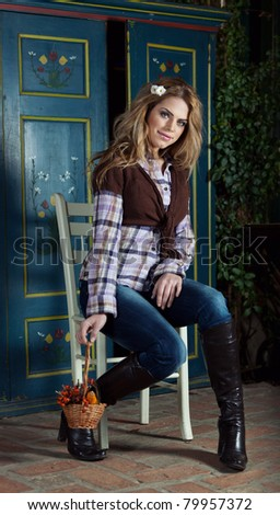 Country style fashion portrait of a beautiful long-haired blond young woman posing indoors.