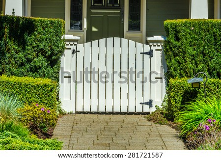 Country style gate, wicket to the house entrance with nicely trimmed and landscaped front yard.