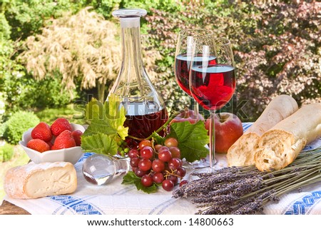 Country-style setting with wine, fruit, bread and cheese