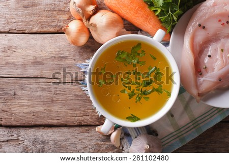 Country style: the chicken broth and the ingredients on the table. vertical view above, homemade food