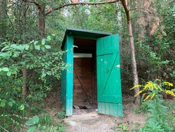 Country toilet in the open air. Wooden structure for outdoor toilet. Cabin - Toilet in the woods in nature.
