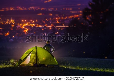 Countryside Camping with Scenic City View Down the Valley. Illuminated Cityscape at Night and the Camper with Illuminated Tent. Countryside Getaway.