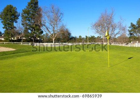 Countryside golf course with green grass, trees and wooden fence