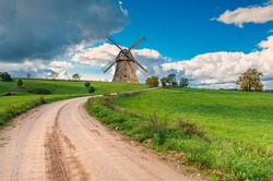 Countryside gravel road among spring field and old windmill on horizon. Concept of ecological tourism in Baltic countries