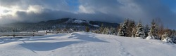 Countryside hills, groves and farmlands in winter remote alpine mountain village. Panorama.