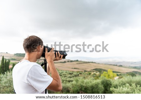 Countryside in Tuscany, Italy with rolling green hills with farm landscape and young man tourist photographer taking picture with camera