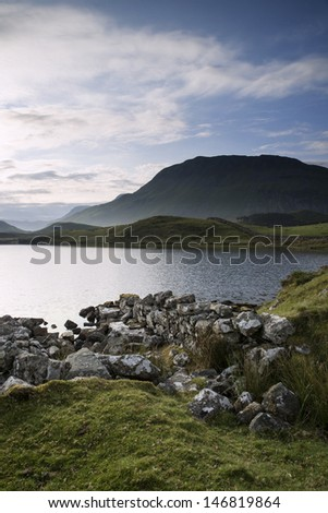 Countryside landscape and mountains in beautiful morning light reflected in calm Cregennen Lakes in Snwodonia National Park