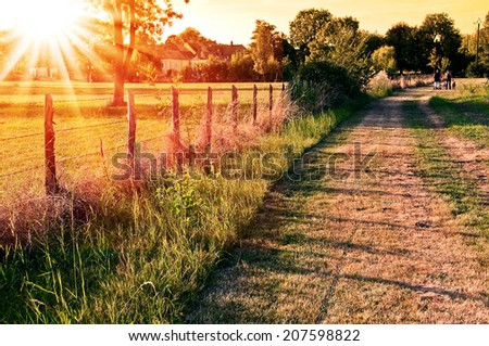 Countryside landscape with a field and a village in the sunset