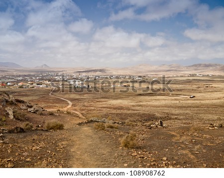 Countryside landscape with desert hills and village in light haze under cloudy sky.