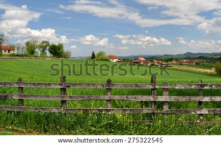 Countryside landscape with lush green grass and wooden fence