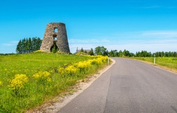 Countryside landscape with road and old windmill ruin. Estonia, Baltic States, Europe