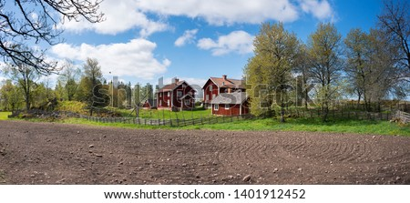 Countryside living idyll - Rural Swedish idyllic landscape in springtime - Red painted houses and plowed fields in the travel destination Asens By in Smaland Sweden. #1401912452