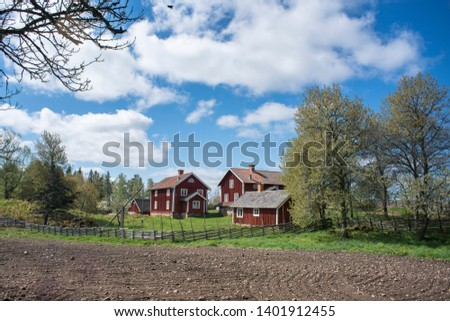 Countryside living idyll - Rural Swedish idyllic landscape in springtime - Red painted houses and plowed fields in the travel destination Asens By in Smaland Sweden. #1401912455