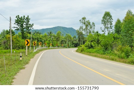 Countryside road with warning curve road sign