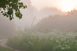Countryside sand road and old wooden leaning cross between tall green grass and trees in thick fog at sunrise