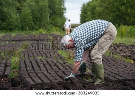 County Kerry, Ireland - May 31, 2014: Workers cultivating a peak bog field outside the town of Listowel in County Kerry #303249035
