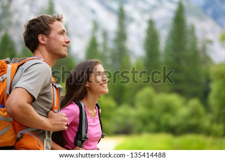 Shutterstock Couple - active hikers hiking enjoying view looking at mountain forest landscape in Yosemite National Park, California, USA. Happy multiracial outdoors couple, young Asian woman and Caucasian man.