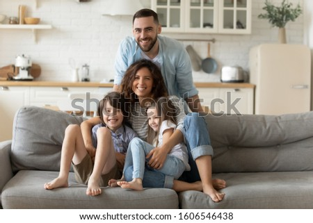 Couple and little children lovely daughter and son posing looking at camera gathered together in modern living room seated on couch photo shooting in studio apartments, happy family portrait concept