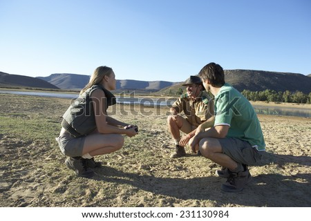 Couple and Safari Guide Looking at Animal Tracks