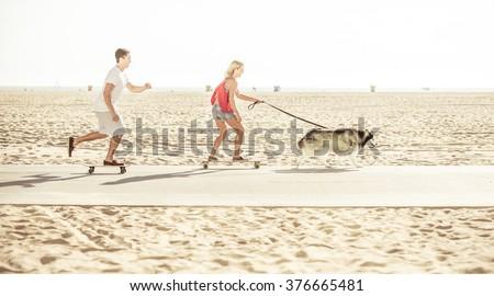 Couple and their husky dog making some sport on the beach with skateboards, Santa monica beach, California