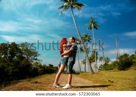 couple are hugging on the background with palm trees #572303065
