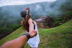 Couple Asian travel nature. Travel relax. happy and enjoying a beautiful nature on peak of foggy mountain. Lover women and men Hold hands running on the lawn. Wild nature wood on the mountain.