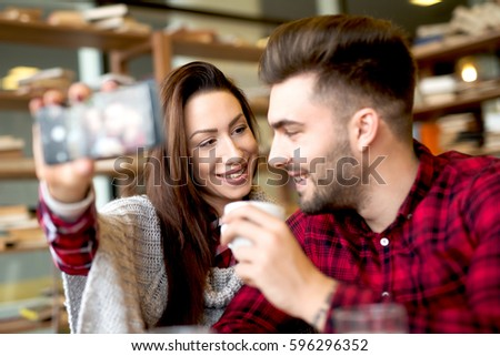 Couple at cafe bar making selfie with smart phone. Friendship concept together doing stuffs. #596296352