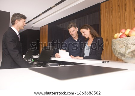 Couple at hotel reception reading bill