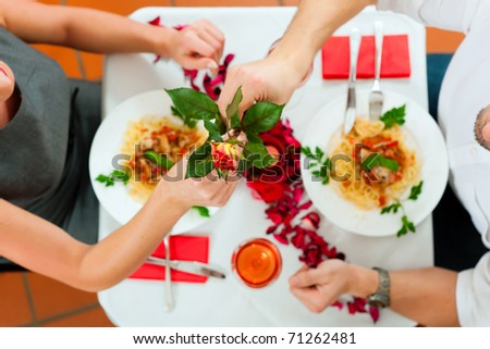 Couple at lunch or dinner; he is giving her a rose