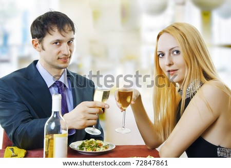 Couple at restaurant on dinner party. They're looking at the shot and raise a toast.