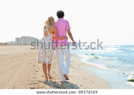 Couple at the beach holding hands and walking. Sunny day, bright colors. Europe, Spain, Costa Blanca. Photo from Behind